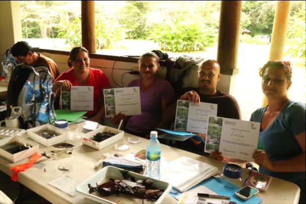 Miembros de la comunidad que muestra con orgullo sus certificados por haber completado exitosamente el taller. Foto por, Erin Engbeck